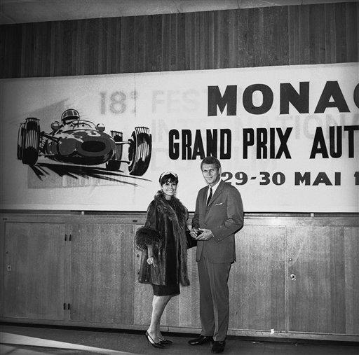Steve McQueen and his wife Nellie are seen in front of a poster advertising the Monaco grand prix automobile race of Sunday in Monaco May 29, 1965. McQueen arrived in Monaco to watch the car race and to look for location for his next film to deal with races. (AP Photo/Maestri)