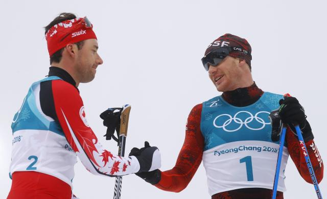 Cross-Country Skiing - Pyeongchang 2018 Winter Olympics - Men's 50km Mass Start Classic - Alpensia Cross-Country Skiing Centre - Pyeongchang, South Korea - February 24, 2018 - Alex Harvey of Canada and Dario Cologna of Switzerland react at the finish line. REUTERS/Kai Pfaffenbach
