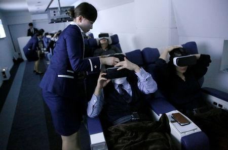"Staff dressed as flight attendants, help guests to wear virtual reality (VR) goggles at the ""First Airlines"", virtual first-class airline experience facility in Tokyo, Japan February 14, 2018. Picture taken February 14, 2018.  REUTERS/Toru Hanai"