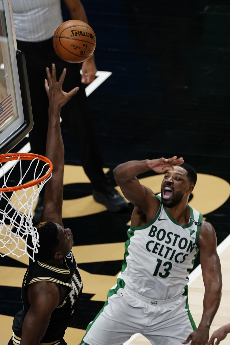Boston Celtics forward Tristan Thompson (13) reacts as he shots against Atlanta Hawks center Clint Capela (15) in the first half of an NBA basketball game Wednesday, Feb. 24, 2021, in Atlanta. (AP Photo/John Bazemore)