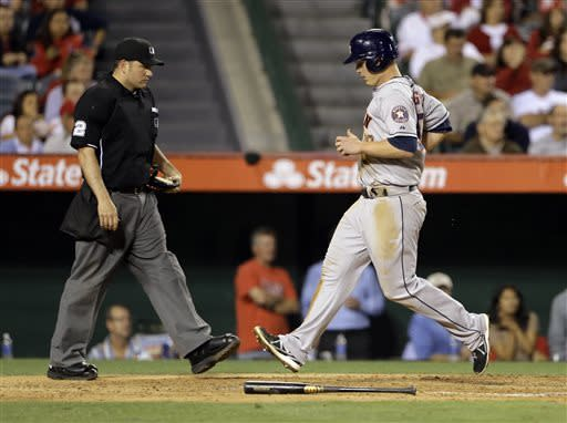 Home plate umpire Dan Bellino watches as Houston Astros' Matt Dominguez scores on a Brandon Barnes sacrifice fly against the Los Angeles Angels in the sixth inning of a baseball game in Anaheim, Calif., Monday, June 3, 2013. (AP Photo/Reed Saxon)