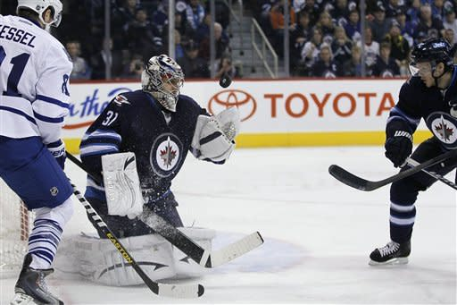 Winnipeg Jets goaltender Ondrej Pavelec (31) reaches out for the puck as as Tobias Enstrom (39) and Toronto Maple Leafs' Phil Kessel (81) look for the rebound during second period NHL action in Winnipeg on Thursday, Feb. 7, 2013. (AP Photo/The Canadian Press, John Woods)