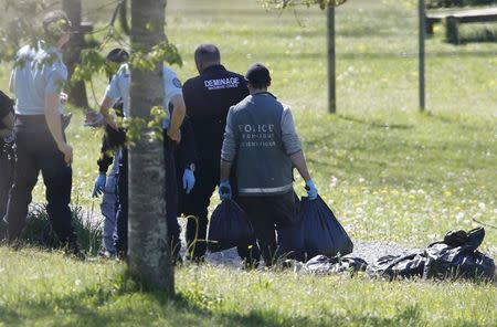 French police and gendarmerie officers carry bags with evidences and weapons during investigations in Saint-Pee-sur-Nivelle