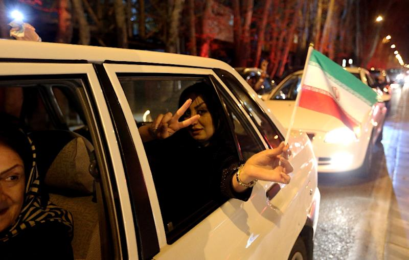 A woman in a car waves an Iranian flag as people celebrate on Valiasr street in northern Tehran on April 2, 2015, after the announcement of an agreement on Iran nuclear talks