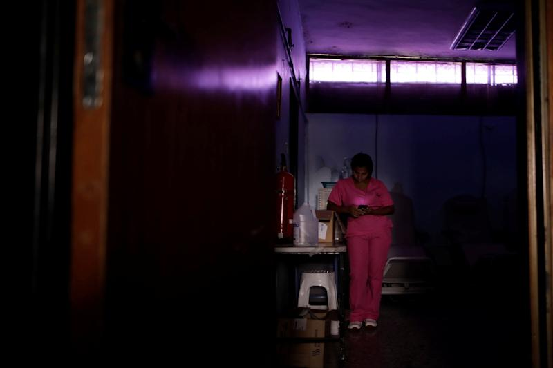 A nurse uses a mobile phone while she waits for the electricity to return in a dialysis center during a blackout in Maracaibo, Venezuela. (Photo: Ueslei Marcelino/Reuters)