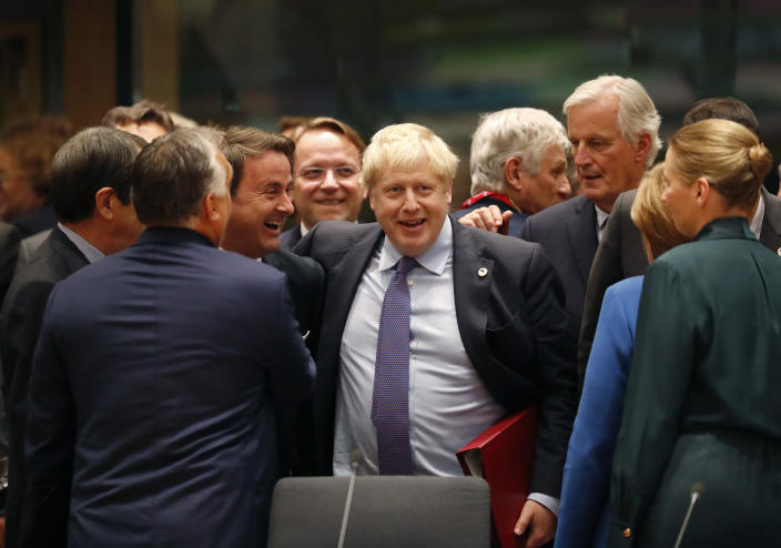 FILE - In this Thursday, Oct. 17, 2019 file photo British Prime Minister Boris Johnson, center, is greeted by Luxembourg's Prime Minister Xavier Bettel, center left, during a round table meeting at an EU summit in Brussels. (AP Photo/Frank Augstein)
