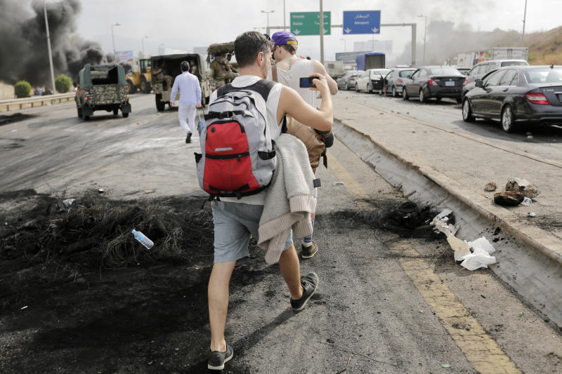 Passengers walk to airport as anti-government protesters blocked the road to the airport with burning tires during a protest against government's plans to impose new taxes in Beirut, Lebanon, Friday, Oct. 18, 2019. Demonstrators in Lebanon are blocking major roads across the country in a second day of protests against proposed new taxes, which come amid a severe economic crisis. (AP Photo/Hassan Ammar)