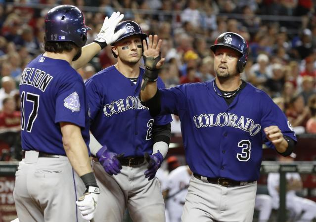 Colorado Rockies' Todd Helton (17) gives a high-five to Michael Cuddyer (3) as Troy Tulowitzki (2) looks on after both Cuddyer and Tulowitzki score runs against the Arizona Diamondbacks in the seventh inning of a baseball game on Friday, Sept. 13, 2013, in Phoenix. The Rockies defeated the Diamondbacks 7-5. (AP Photo/Ross D. Franklin)