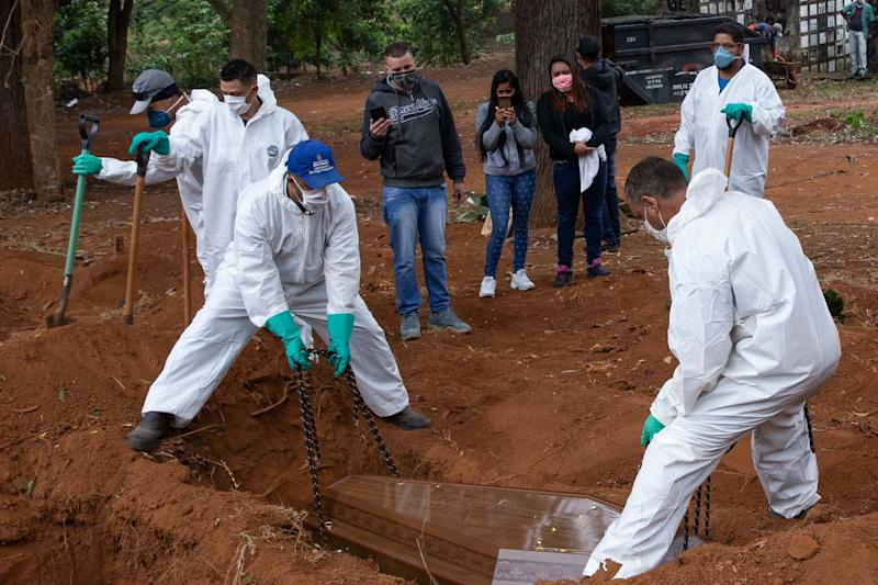 Adenilson Souza Costa, 47 years, and his coworkers wearing protective gear bury a coffin during a burial at Vila Formosa Cemetery in Sao Paulo (Getty Images)