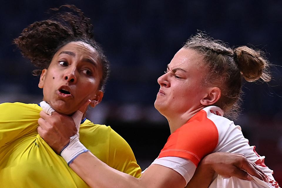 <p>Brazil's centre back Ana Paula Rodrigues Belo (L) is grabbed by Hungary's pivot Reka Bordas during the women's preliminary round group B handball match between Brazil and Hungary of the Tokyo 2020 Olympic Games at the Yoyogi National Stadium in Tokyo on July 27, 2021. (Photo by Daniel LEAL-OLIVAS / AFP)</p>