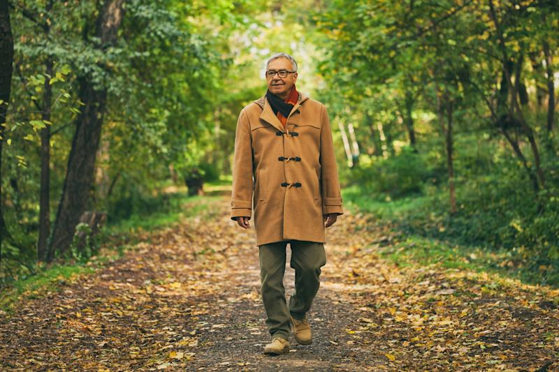 Older man in a coat, walking on a paved path surrounded by early-autumn woods