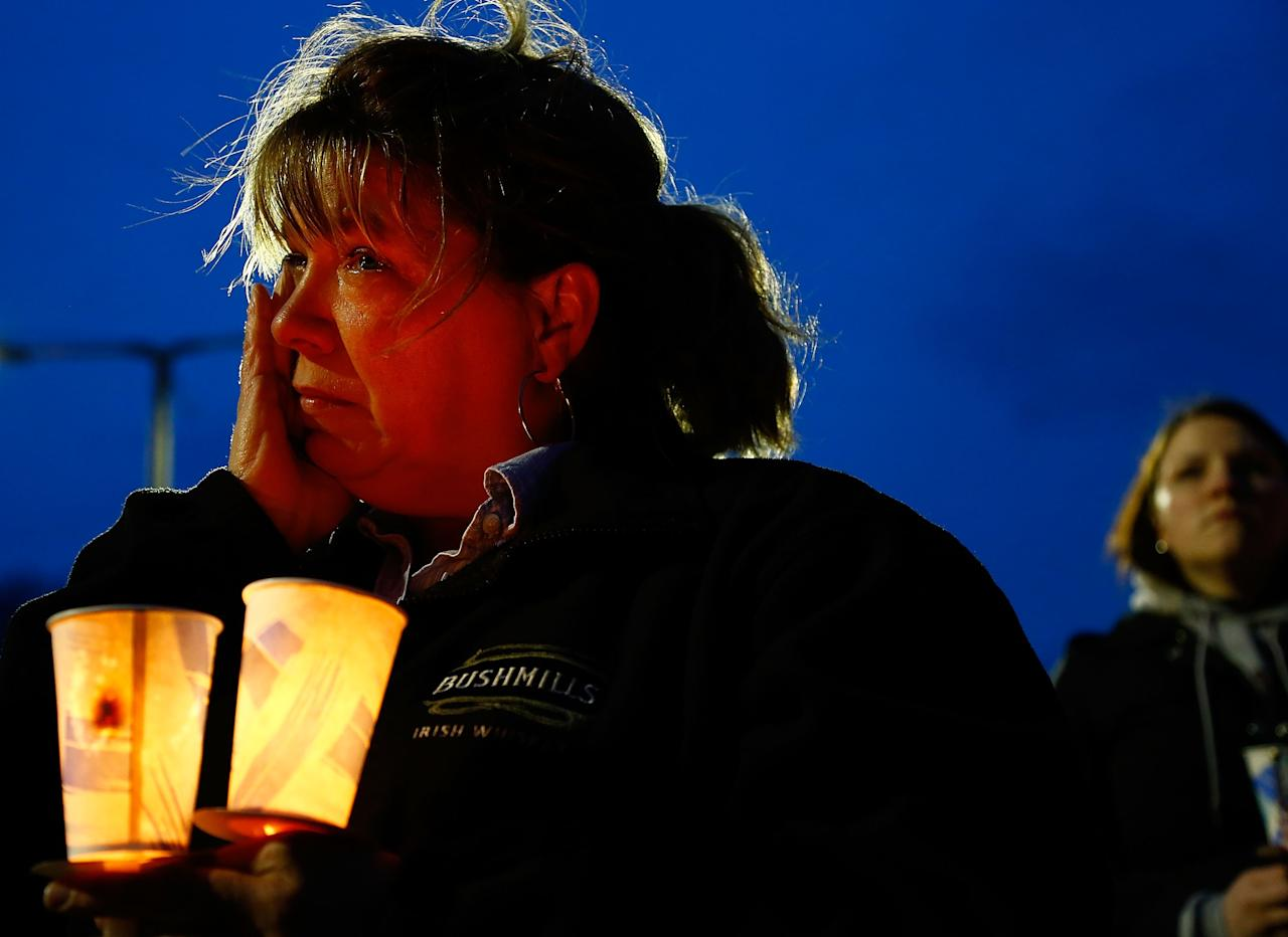 BOSTON, MA - APRIL 16: A woman cries while listening during the vigil for eight-year-old Martin Richard, from Dorchester, who was killed by an explosion near the finish line of the Boston Marathon on April 16, 2013 at Garvey Park in Boston, Massachusetts. The twin bombings resulted in the deaths of three people and hospitalized at least 128. The bombings at the 116-year-old Boston race resulted in heightened security across the nation with cancellations of many professional sporting events as authorities search for a motive to the violence. (Photo by Jared Wickerham/Getty Images)