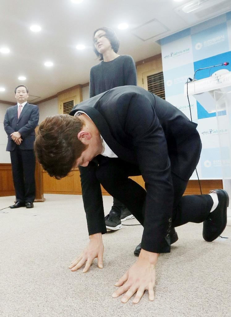 South Korean swimmer Park Tae-Hwan makes a formal deep bow to express his regret for doping (AFP Photo/YONHAP)