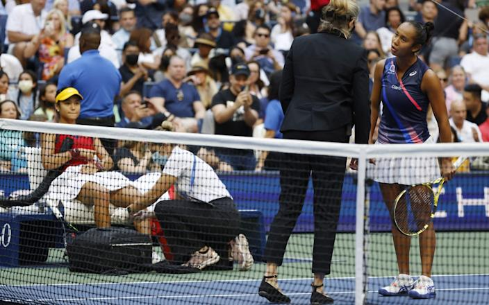 Lelyah Fernandez of Canada (R) talks with an official as Emma Raducanu of Great Britain receives medical treament for a bloody knee during the women's final match - Shutterstock