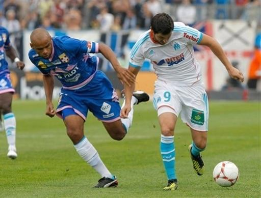 Evian's French defender Aldo Angoula, left, challenges for the ball with Marseille's French forward Andre-Pierre Gignac, during their League One soccer match, at the Velodrome stadium, in Marseille, southern France, Sunday, Sept. 23, 2012. (AP Photo/Claude Paris)