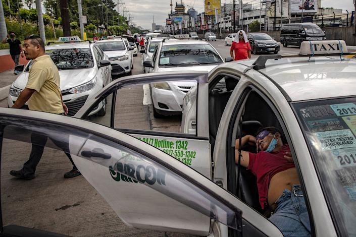 Apprehended taxis are parked along a major highway after authorities cracked down on public transportation as part of measures to prevent the spread of COVID-19 on March 17, 2020 in Quezon city, Metro Manila, Philippines.
