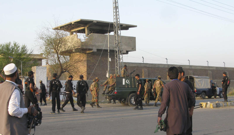 """Pakistan army soldiers and other security officials surround a central jail in Bannu, 170 kilometers (106 miles) south of Peshawar, Pakistan on Sunday, April 15, 2012. Taliban militants battled their way into the prison in northwest Pakistan on Sunday, freeing close to 400 prisoners, including at least 20 described by police as """"very dangerous"""" insurgents, authorities and the militants said. (AP Photo Ijaz Muhammad)"""