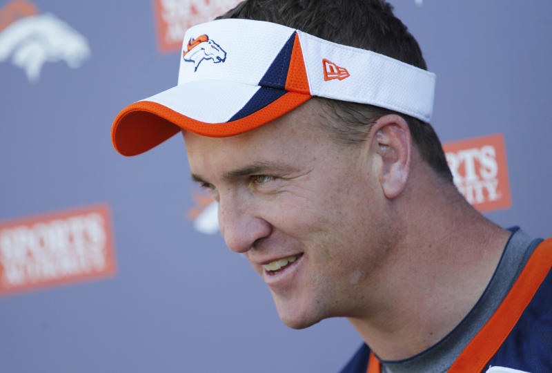 Denver Broncos starting quarterback Peyton Manning jokes with reporters after taking part in the morning session at the team's NFL training camp in Englewood, Colo., on Tuesday, Aug. 6, 2013. (AP Photo/David Zalubowski)
