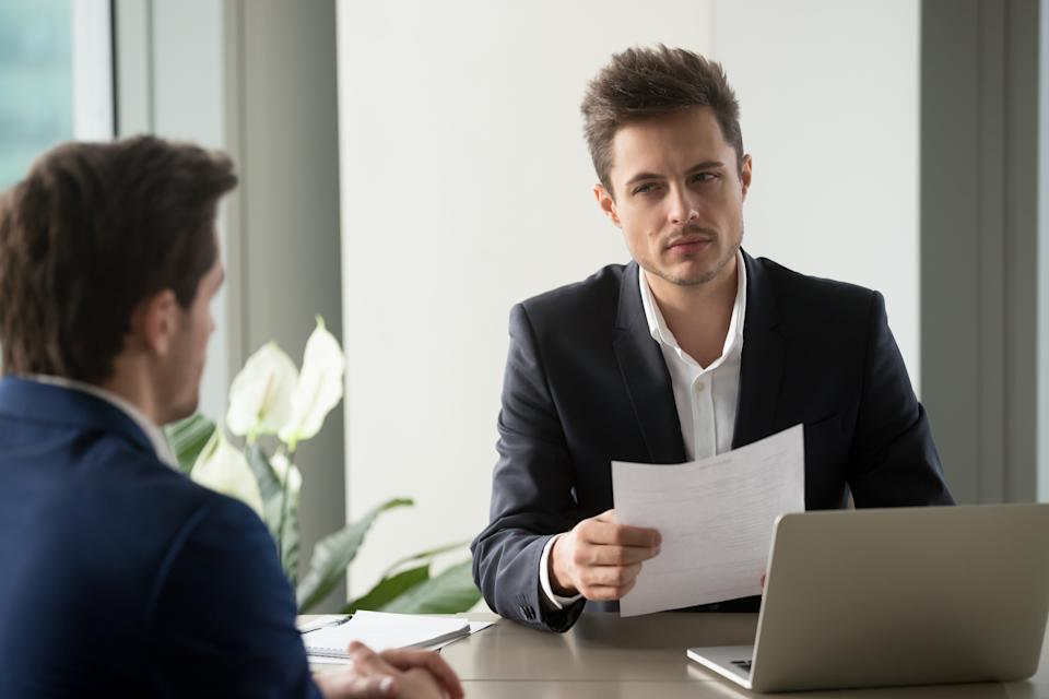 Distrustful businessman holding document at meeting, looking at partner with doubt suspicion, recruiter reads bad resume, caught applicant being dishonest at job interview, shady deal, contract fraud
