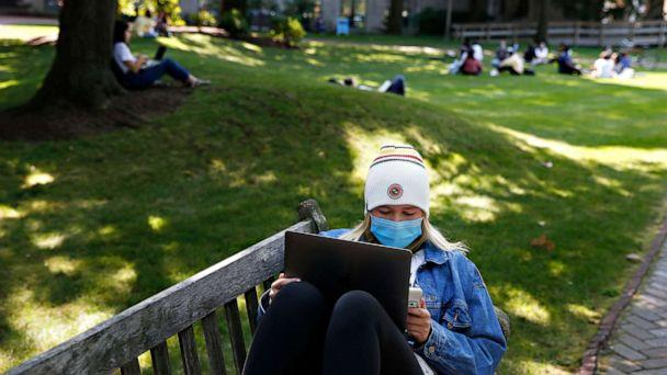 PHOTO:A student wears a mask as she works on her laptop outside on the BU Beach at Boston University in Boston on Sept. 23, 2020. (Boston Globe via Getty Images)