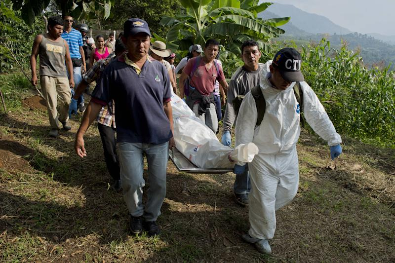 Residents and policemen carry the corpses of five soldiers killed by the Revolutionary Armed Forces of Colombia (FARC) guerrilla during combat in a rural area of Santander de Quilichao, Department of Cauca, Colombia, on December 19, 2014 (AFP Photo/Luis Robayo)