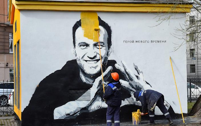 """A worker paints over graffiti of jailed Kremlin critic Alexei Navalny in Saint Petersburg. The inscription reads: """"The hero of the new times."""" - OLGA MALTSEVA/AFP"""