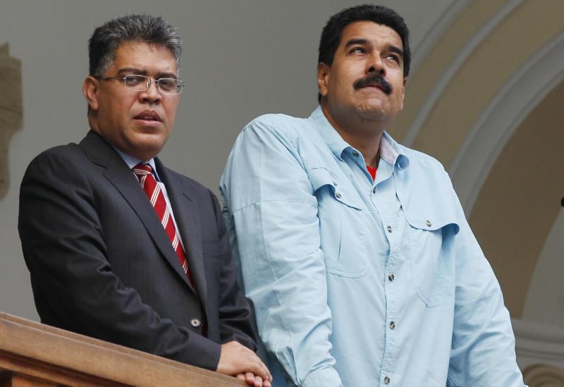 """Venezuela's President Nicolas Maduro, right, and Foreign Minister Elias Jaua, stand on the balcony of the Foreign Ministry after meeting with South Africa's foreign minister, in Caracas, Venezuela, Thursday, Sept. 19, 2013. Jaua said Thursday that the United States has prohibited a planned flight by Maduro from passing through U.S. airspace over Puerto Rico. The foreign minister said that the flight had been scheduled to pass over the U.S. territory on Friday on its way to China. He characterized the U.S. action as an """"aggression."""" (AP Photo/Ariana Cubillos)"""
