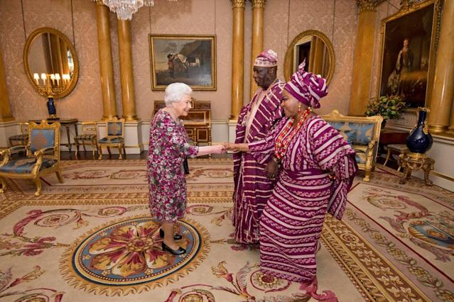 The Queen greeted George Adesola Oguntade and his wife Modupe at Buckingham Palace. (Photo: Getty Images)
