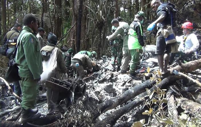 Indonesian rescuers search through wreckage of the Trigana Air ATR 42-300 twin-turboprop plane at the crash site in the mountainous area of Oksibil on August 18, 2015 (AFP Photo/STR)