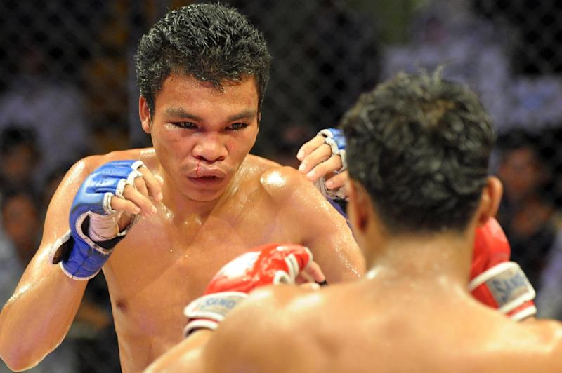 Two men take part in a Cambodian cage fight for a local television programme at a stadium in Phnom Penh, August 24, 2014 (AFP Photo/Tang Chhin Sothy)
