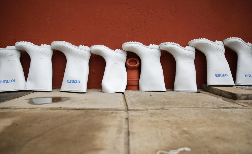 The rubber boots of medical workers stand in a line to dry after being decontaminated at an isolation and treatment center for those with COVID-19 in Machakos, south of the capital Nairobi, in Kenya Tuesday, Nov. 3, 2020. As Africa is poised to surpass 2 million confirmed coronavirus cases it is Kenya's turn to worry the continent with a second surge in infections well under way. (AP Photo/Brian Inganga)
