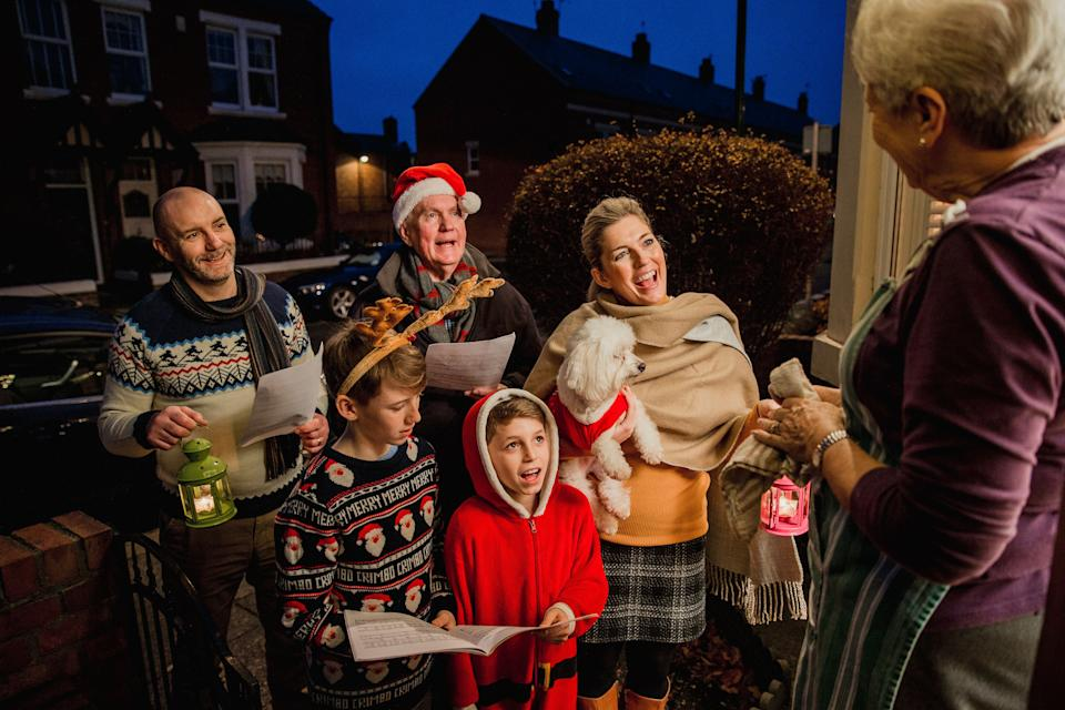 Three generation family are doing door-to-door carol singing. There is a senior woman at the door, appreciating their singing. (Photo: DGLimages via Getty Images)