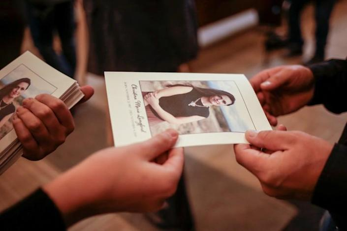 Relatives of Christina Marie Langford Johnson, who was killed by unknown assailants, deliver prayer pamphlets with a picture of Christina during her funeral service, before a burial at the cemetery in LeBaron, Chihuahua