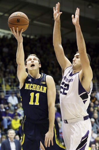 CORRECTS TO MICHIGAN GUARD NIK STAUSKAS NOT TIM HARDAWAY JR. - Michigan guard Nik Stauskas, left, drives to the basket as Northwestern center Alex Olah guards during the first half of an NCAA college basketball game in Evanston, Ill., Thursday, Jan. 3, 2013. (AP Photo/Nam Y. Huh)