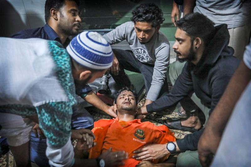 Locals help a Bangladeshi firefighter who lost consciousness briefly while trying to douse flames of a smoldering fire in a building in Dhaka, Bangladesh, Feb. 21, 2019. (Photo: Zabed Hasnain Chowdhury/AP)