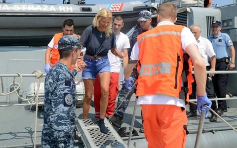 Kay Longstaff is escorted by rescuers from a Croatian Coast Guard vessel in the port of Pula - Credit: AP