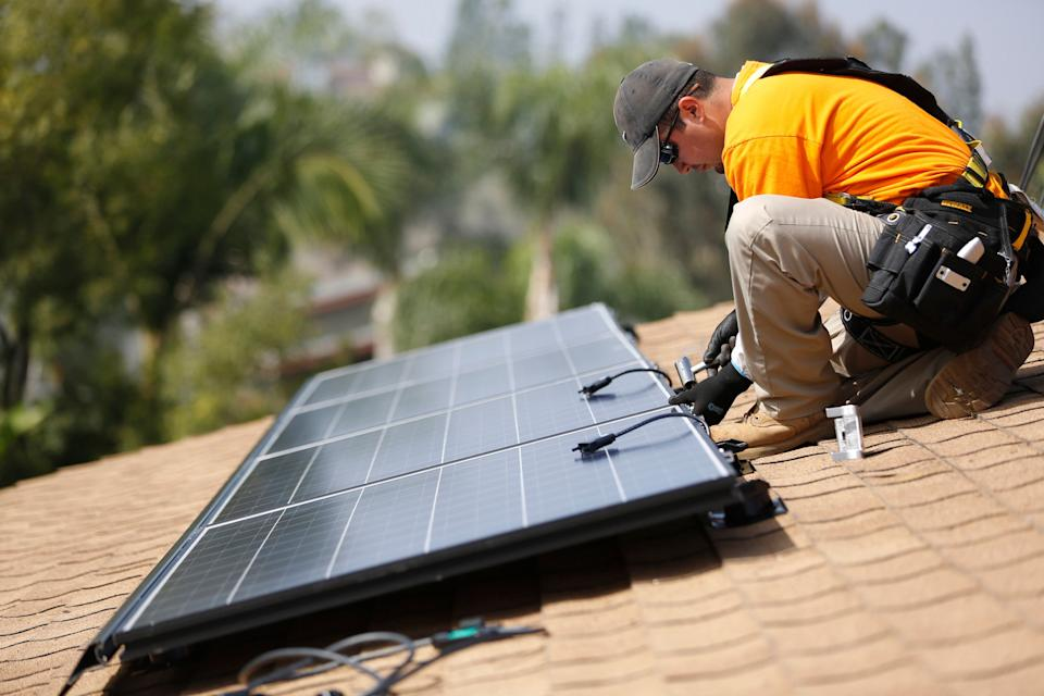 Vivint Solar technician Eduardo Aguilar installs solar panels on the roof of a house in Mission Viejo, Calif. (Photo: REUTERS/Mario Anzuoni)