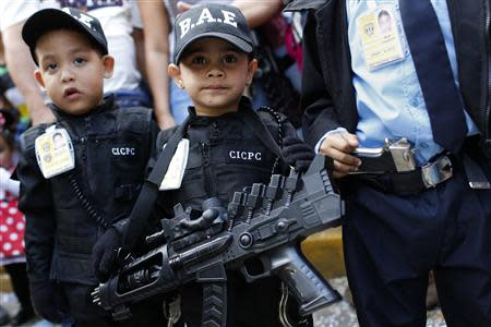 Children dressed as police officers parade during the Carnival festival in Caracas March 4, 2014. REUTERS/Carlos Garcia Rawlins