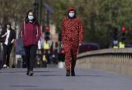 People wear protective face masks as they walk in Westminster in London, as the country is in lockdown to help curb the spread of coronavirus, Tuesday, April 21, 2020. (AP Photo/Kirsty Wigglesworth)