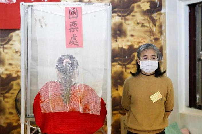 A Taiwanese voter stands at a polling booth during the general elections in Kaohsiung