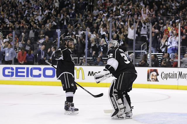 Los Angeles Kings defenseman Drew Doughty, left, celebrates a win against the Chicago Blackhawks with goalie Jonathan Quick after Game 3 of the Western Conference finals of the NHL hockey Stanley Cup playoffs in Los Angeles, Saturday, May 24, 2014. (AP Photo/Chris Carlson)