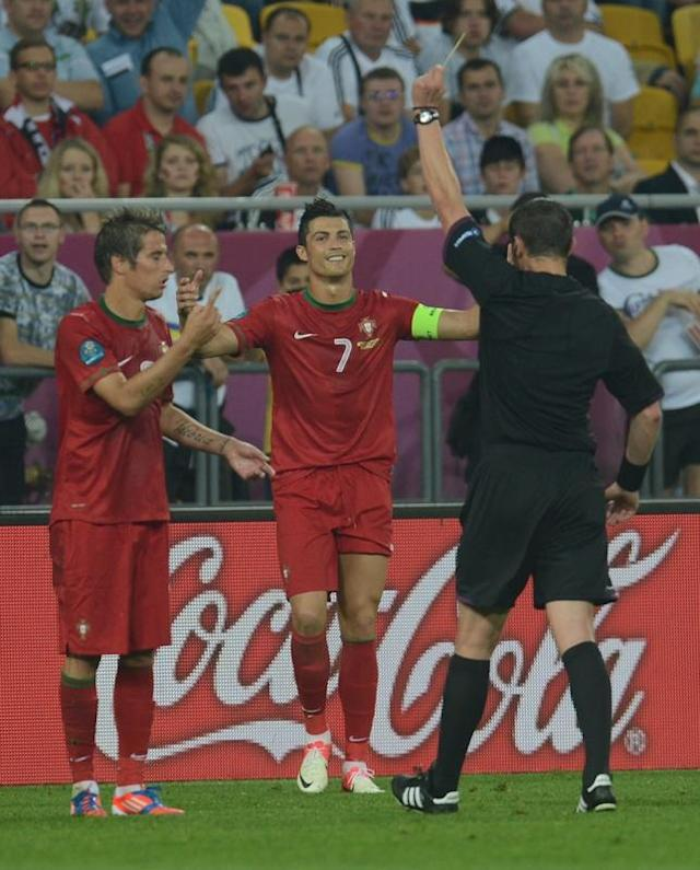 The French referee Stephane Lannoy (R) gives a yellow card to Portuguese defender Fabio Coentrao during the Euro 2012 championships football match Germany vs Portugal on June 9, 2012 at the Arena Lviv. AFP PHOTO / PATRIK STOLLARZPATRIK STOLLARZ/AFP/GettyImages