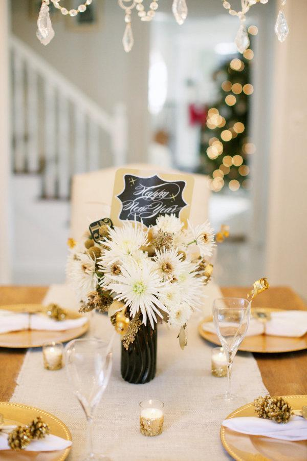 """<p>As a new year blossoms, add a bit of spirited, springy decor to your dinner party (it'll be especially well-welcomed if you live in a snowy climate!). In this tablescape from <a rel=""""nofollow noopener"""" href=""""http://www.stylemepretty.com/vault/image/841419"""" target=""""_blank"""" data-ylk=""""slk:Style Me Pretty Living"""" class=""""link rapid-noclick-resp"""">Style Me Pretty Living</a>, a black vase anchors wildly arranged gold and white blossoms and a """"Happy New Year"""" sign. </p>"""