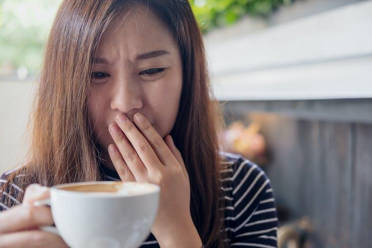 A woman disgusted at the smell of a cup of coffee