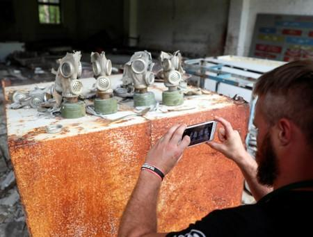 A visitor takes a picture of gas masks at a former base of the Soviet army, near the Chernobyl Nuclear Power Plant