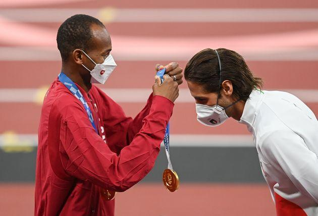 Gold medalist Mutaz Essa Barshim of Qatar, left, presents Gianmarco Tamberi of Italy with his gold medal during the men's high jump medal ceremony at the Olympic Stadium on Day 10 of the 2020 Tokyo Summer Olympic Games in Tokyo, Japan. The two athletes decided to <a href=