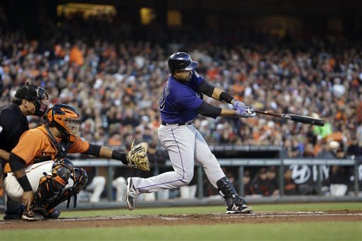 Colorado Rockies' Wilin Rosario hits a double off San Francisco Giants starting pitcher Tim Lincecum during the second inning of a baseball game in San Francisco, Friday, Aug. 10, 2012. (AP Photo/Tony Avelar)
