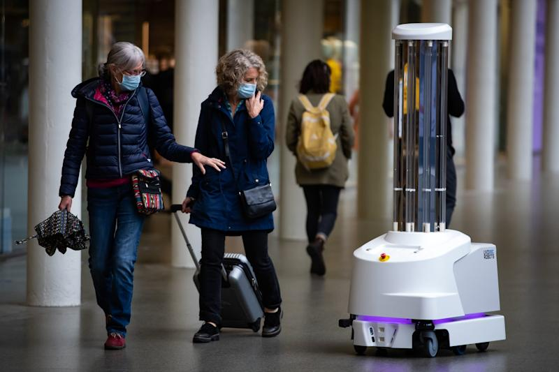 Travellers point at the new cleaning robots (PA)