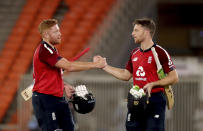England's Jonny Bairstow, left, and Jos Buttler celebrate their win in the third Twenty20 cricket match between India and England at Narendra Modi Stadium in Ahmedabad, India, Tuesday, March 16, 2021. (AP Photo/Aijaz Rahi)
