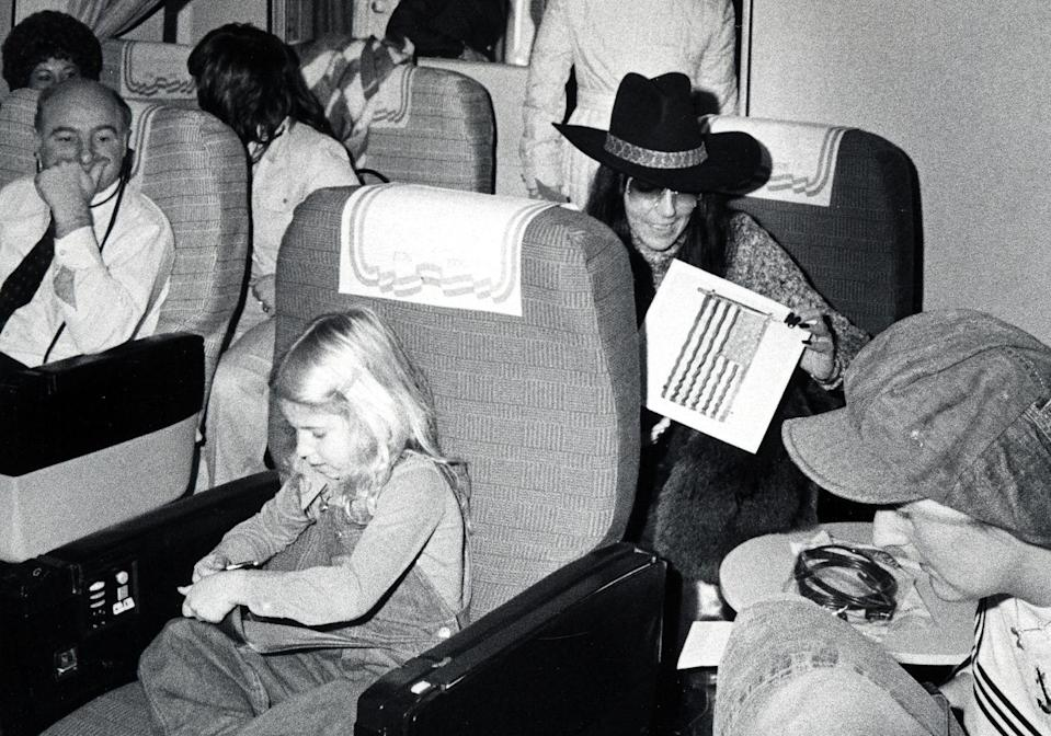 <p>Cher takes a flight to Los Angeles with Chastity (now Chaz) Bono in 1975. </p>
